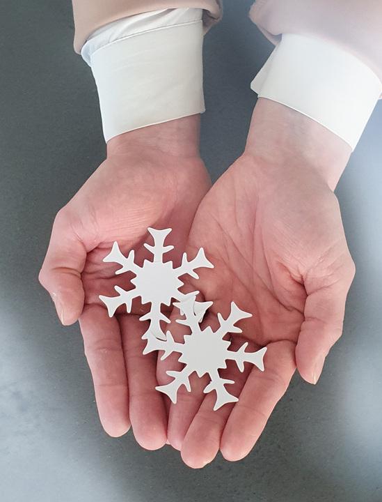 Hände halten Schneeflocken